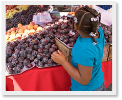 Young girl selecting produce at farmers market.